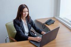 Młody pomocniczy działanie w biurze przy laptopem obraz royalty free