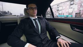 Młody pomyślny biznesmen iść spotykać w luksusowym samochodzie, ruch drogowy w mieście zbiory