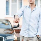 Młody pomyślny biznesmen oferuje samochodowego klucz Obraz Royalty Free