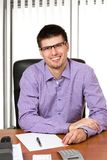 Młody pomyślny biznesmen pracuje przy jego biurkiem zdjęcia stock