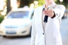 Młody pomyślny bizneswoman oferuje samochodowego klucz fotografia stock