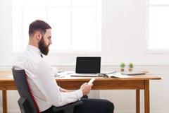 Młody pomyślny broda biznesmen w koszula z laptopem i telefonem komórkowym w nowożytnym białym biurze Obraz Stock