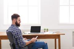 Młody pomyślny broda biznesmen z laptopem i telefonem komórkowym w nowożytnym białym biurze Zdjęcie Royalty Free