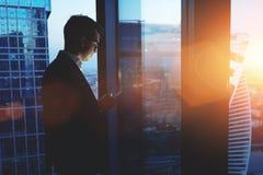 Młody pomyślny mężczyzna przedsiębiorcy telefon komórkowy podczas gdy stojący w drapacza chmur biurowym wnętrzu przy zmierzchem, Obrazy Royalty Free