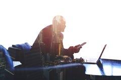 Młody pomyślny męski przedsiębiorca pracuje na cyfrowej pastylce i laptopie Zdjęcia Royalty Free