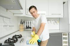 Młody poważny mężczyzna jest ubranym gumowe żółte rękawiczki czyści stov zdjęcia royalty free