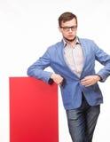 Młody poważny mężczyzna pokazuje prezentację, wskazuje na plakacie Fotografia Royalty Free