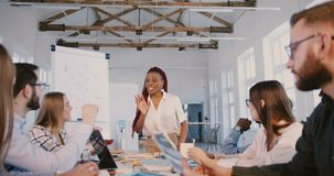 Młody pozytywny amerykanin afrykańskiego pochodzenia biznesowej kobiety trener mówi wieloetniczni pracownicy przy pieniężnym semi zbiory wideo