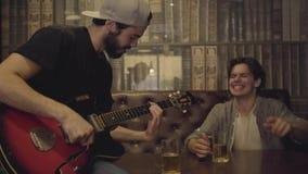 Młody pozytywny brodaty mężczyzna bawić się gitarę w barze, jego męski przyjaciel siedzi blisko trząść jego kierowniczego w rytmu zbiory
