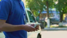 Młody pracownik bierze pieniądze dla drobnicowej doręczeniowej studenckiej na pół etatu pracy i liczy zbiory