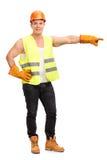 Młody pracownik budowlany wskazuje z ręką Fotografia Royalty Free