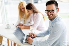 Młody pracownik pracuje na komputerze podczas pracującego dnia w biurze Zdjęcie Stock