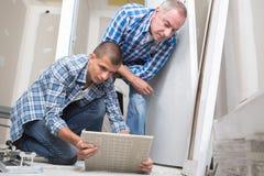 Młody pracownik umieszcza płytki podłoga z nadzorcą zdjęcie stock