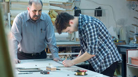 Młody praktykant buduje ramę za biurkiem w ramowym warsztacie Zdjęcia Royalty Free