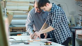 Młody praktykant próbuje ciąć szkło dla ramy, seniour pracownika dopatrywanie Obraz Royalty Free