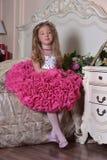Młody princess w eleganckiej menchii ubiera obsiadanie fotografia stock
