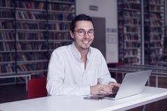 Młody przedsiębiorca, student uniwersytetu ono uśmiecha się i pracuje na laptopie z książką na naukowej dyplomówce w bibliotece Obrazy Royalty Free