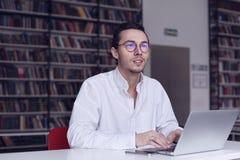 Młody przedsiębiorca, student uniwersytetu pracuje na laptopie z książką na naukowej dyplomówce w bibliotece Obrazy Royalty Free