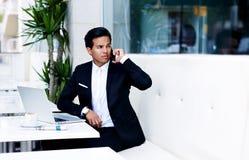 Młody przedsiębiorca w luksusowym czarnym kostiumu ma komórki rozmowę podczas pracy przerwy w kawiarni Obraz Royalty Free
