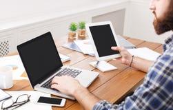 Młody przypadkowy biznesmen pracuje z laptopem i pastylką w biurze, zamyka up Zdjęcia Stock
