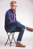 Młody przypadkowy mężczyzna obsiadanie na stolec Zdjęcia Royalty Free