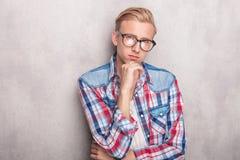 Młody przypadkowy mężczyzna opiera na popielatej ścianie fotografia royalty free