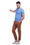 Młody przypadkowy mężczyzna przedstawia coś Zdjęcia Stock