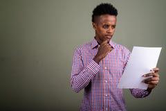 Młody przystojny Afrykański biznesmen przeciw barwionemu tłu obrazy stock