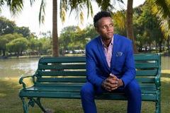 Młody przystojny Afrykański biznesmen relaksuje przy parkiem w Bangk obrazy royalty free