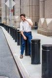 Młody przystojny Amerykański mężczyzna opowiada na telefonie komórkowym outside w Nowym Fotografia Stock