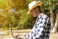 Młody przystojny atrakcyjny mężczyzna obsiadanie na piaskowatej tropikalnej egzot plaży na lato kurorcie pracuje na laptopie fotografia stock
