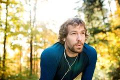 Młody przystojny biegacz z słuchawkami outside w jesieni naturze Obrazy Royalty Free