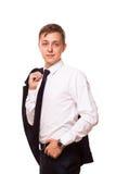 Młody przystojny biznesmen trzyma kurtkę w jego jeden ręce i innej ręce w jego kieszeni portret odizolowywający dalej Obrazy Royalty Free