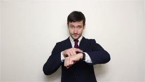 Młody przystojny biznesmen z poważną twarzą wskazuje jego palec przy zegarem zdjęcie wideo