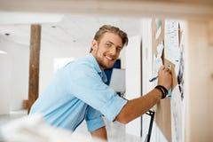 Młody przystojny biznesmena writing na papierze przyczepiał corkboard, patrzeje w kamery ono uśmiecha się Biurowy tło Zdjęcia Stock