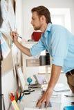 Młody przystojny biznesmena writing przy papierem przyczepiał corkboard Biurowy tło Fotografia Stock
