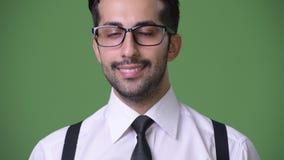Młody przystojny brodaty Perski biznesmen przeciw zielonemu tłu zdjęcie wideo