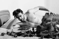 Młody przystojny brodaty sportowy macho mężczyzna z elegancki brody kłamać nagi na łóżku pod czerwoną koc wokoło pomarańczowych r zdjęcie stock