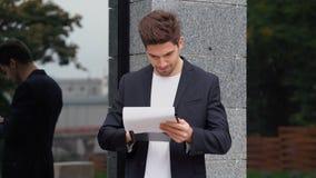 Młody przystojny brunetka mężczyzna w kostium kurtce sprawdza dokumenty, rachunek za usługę komunalną, raport Biznesmen stoi blis zdjęcie wideo