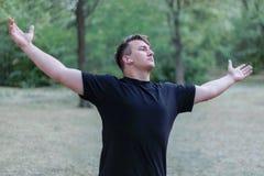Młody przystojny caucasian mężczyzna szeroko rozciąga za jego ręk rękach przy parkowym tłem obraz stock