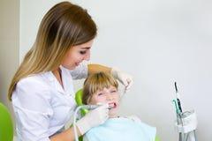 Młody przystojny dentysta taktuje zębu dziecka, kobieta dentysta obraz royalty free