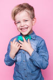 Młody przystojny dzieciak ono uśmiecha się z błękitną koszula i motylim krawatem Pracowniany portret nad różowym tłem Zdjęcia Royalty Free