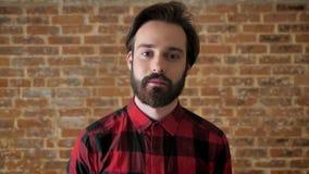 Młody przystojny facet myśleć proces z brodą tworzy pomysł, ono uśmiecha się, ceglany tło zdjęcie wideo