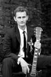 Młody przystojny fornal siedzi gitarę w jego ręce i trzyma obraz royalty free