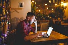 Młody przystojny Kaukaski mężczyzna z brodą i toothy uśmiechem w czerwonej koszula pracuje za laptopem, ręki na klawiaturowym obs fotografia stock