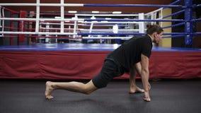 Młody przystojny mężczyzna angażował w bokserskim rozciąganiu i narządzaniu przed głównym szkoleniem Wojownik opracowywa przy gym zbiory