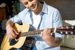 Młody przystojny mężczyzna bawić się gitarę i ono uśmiecha się Obrazy Stock
