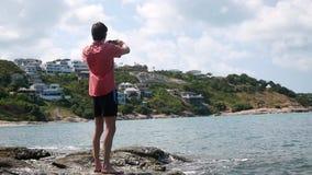 Młody przystojny mężczyzna bierze fotografię z jego mądrze telefonem przy skalistą plażą w chmurnym dniu Koh Samui, Tajlandia swo zbiory wideo