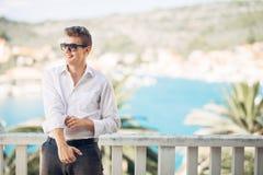 Młody przystojny mężczyzna cieszy się pobyt przy luksusowym hotel w kurorcie z panoramicznym widokiem na morzu zdjęcia stock