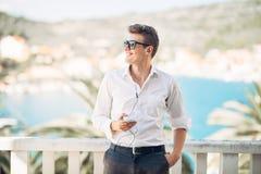 Młody przystojny mężczyzna cieszy się pobyt przy luksusowym hotel w kurorcie z panoramicznym widokiem na morzu zdjęcia royalty free